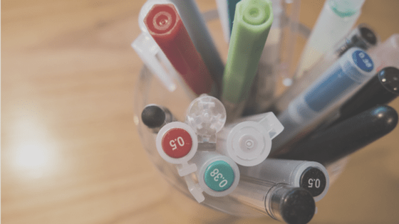 A bunch of pens in a cup.