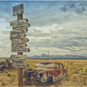 midwest arid countryside with rusted out cars and a wooden signpost