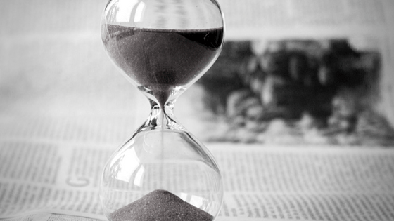Hourglass standing on an open newspaper
