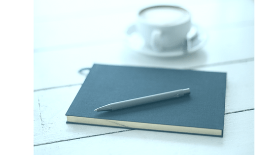 A dark blue notebook, pen, and coffee cup.