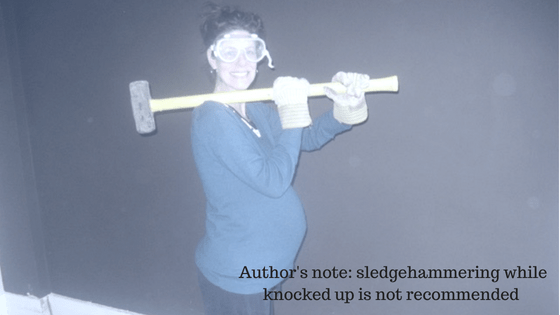 author holding sledgehammer while pregnant at One Lit Place onelitplace.com