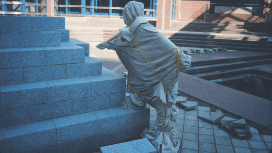 A statue tied under a sheet.