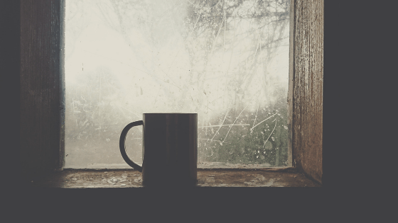 A mug in front of a foggy window.