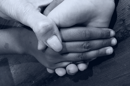 grandmother holding 2 granddaughters' hands