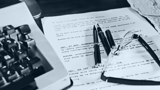 screenplay pages with pens, glasses, and vintage typewriter